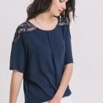 Top bleu foncé avec guipure aux épaules, au style chic et féminin