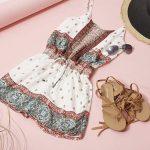 Un joli look d'été avec une robe imprimée style bohème folk, des sandales lacées et un chapeau bicolore