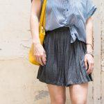 Idée look tendance : jupe grise + chemise à rayures + sac jaune