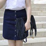 Idée look : top blanc + jupe bleue boutonnée + sac à franges