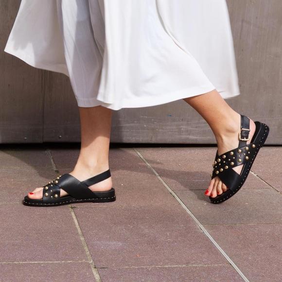 Sandales noires cloutées avec jupe blanche